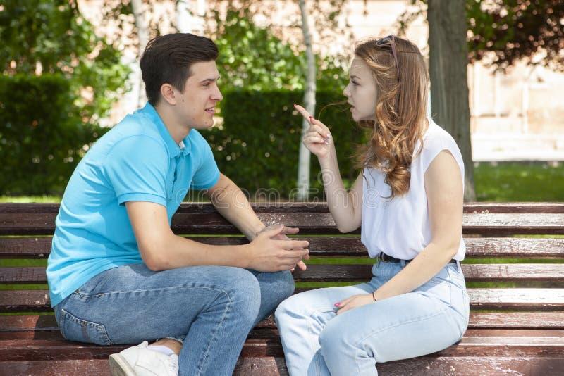 Unga attraktiva par har ett argument över något, utomhus- fors royaltyfri foto