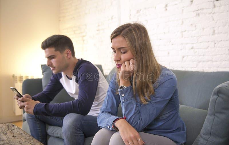Unga attraktiva par i förhållandeproblem med pojkvännen för internetmobiltelefonböjelse som ignorerar ledsen eftersatt och uttråk arkivfoto