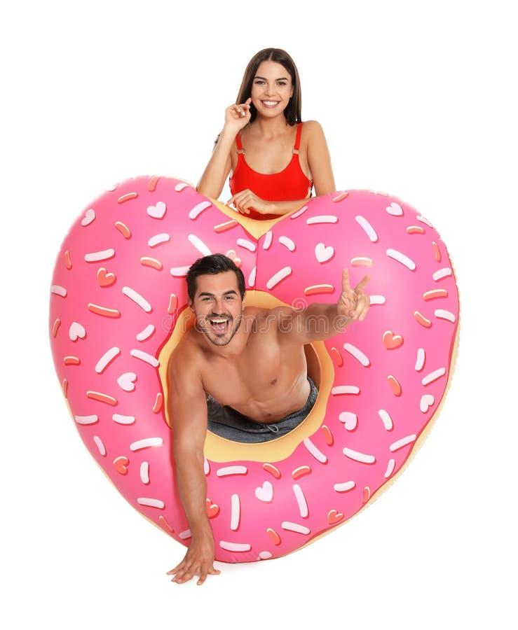 Unga attraktiva par i strandkläder med den uppblåsbara cirkeln på vit arkivbilder