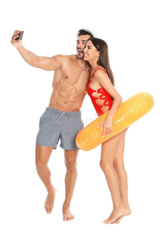 Unga attraktiva par i strandkläder med den uppblåsbara cirkeln som tar selfie på vit arkivfoton