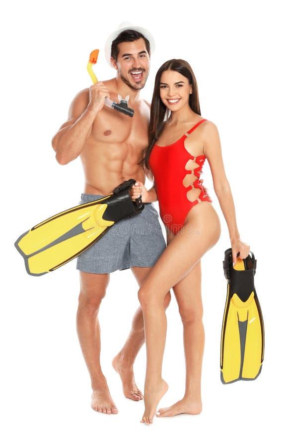 Unga attraktiva par i strandkläder med snorkeln och flipper på vit arkivbilder