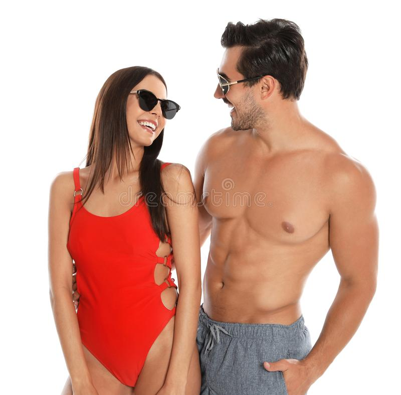 Unga attraktiva par i strandkläder och solglasögon på vit arkivfoto