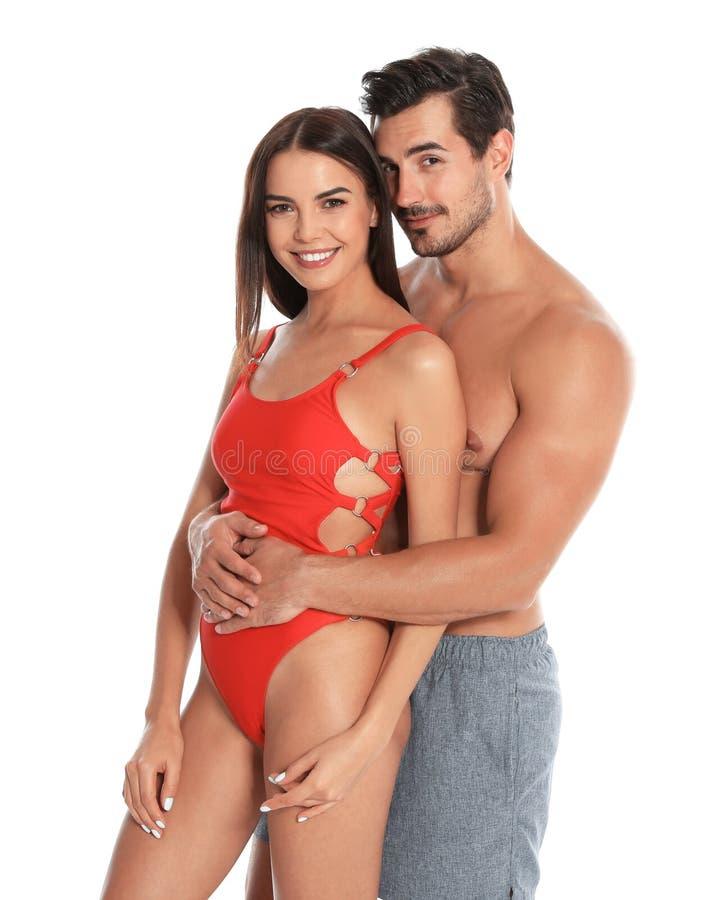 Unga attraktiva par i strandkläder på vit arkivbild