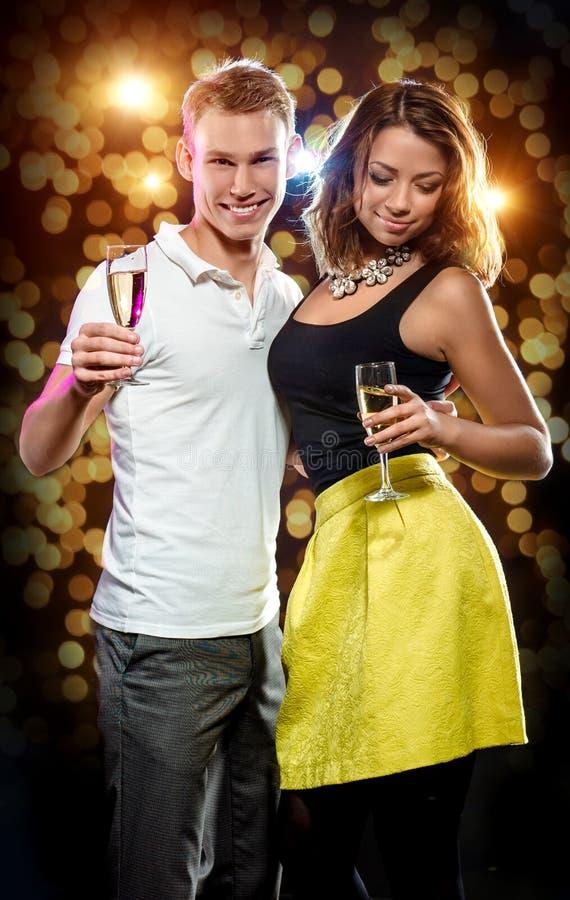 Unga attraktiva par med exponeringsglas av mousserande champagne fotografering för bildbyråer