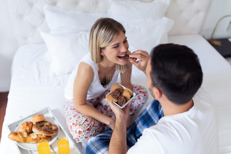Unga attraktiva par som har frukosten i säng arkivbild