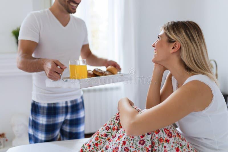 Unga attraktiva par som har frukosten i säng royaltyfria bilder