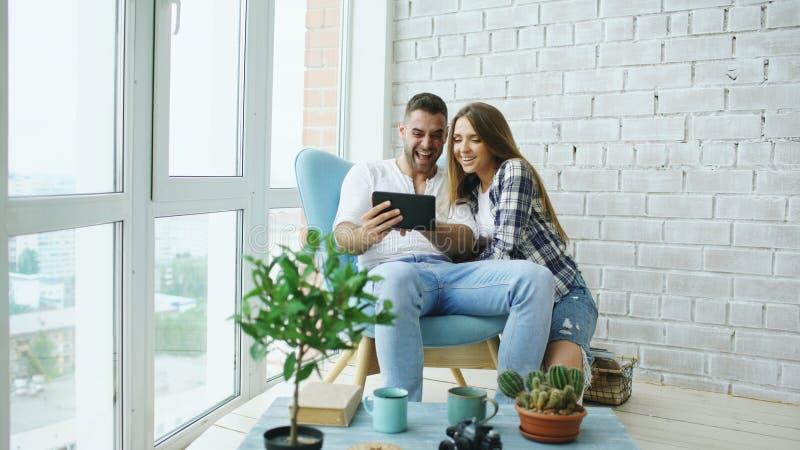 Unga attraktiva par som har online-video pratstund genom att använda minnestavladatorsammanträde på balkongen i modern vindlägenh royaltyfri bild