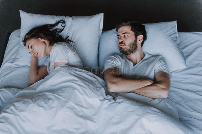 Unga attraktiva par som har problem i säng royaltyfri bild