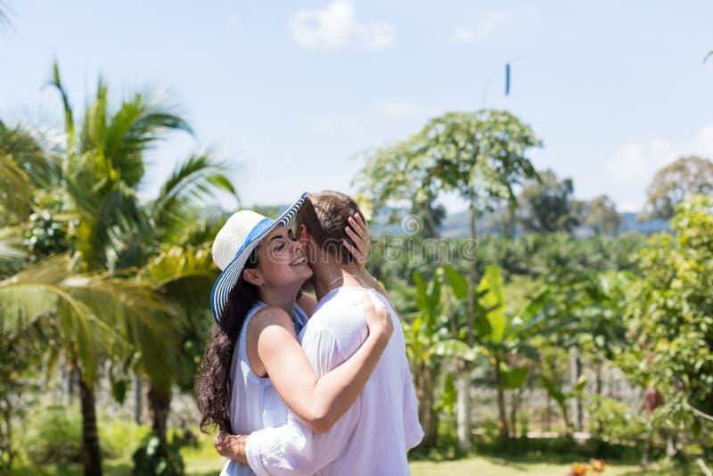 Unga attraktiva par som omfamnar på sommarterrass eller balkong över härligt tropiskt landskap arkivfoton