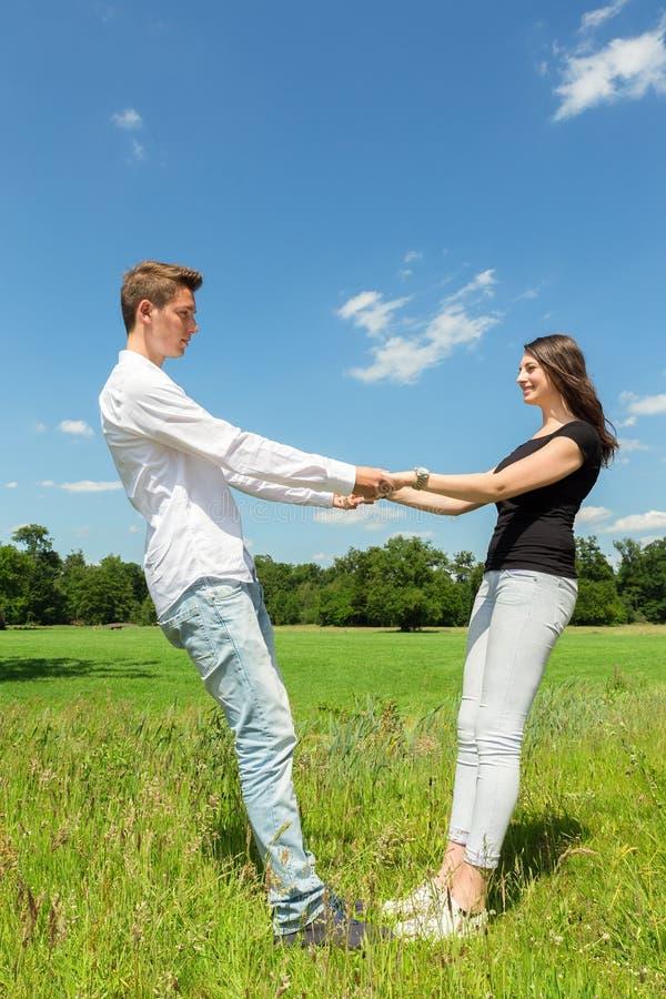 Unga attraktiva par som rymmer sig i solig äng arkivfoton