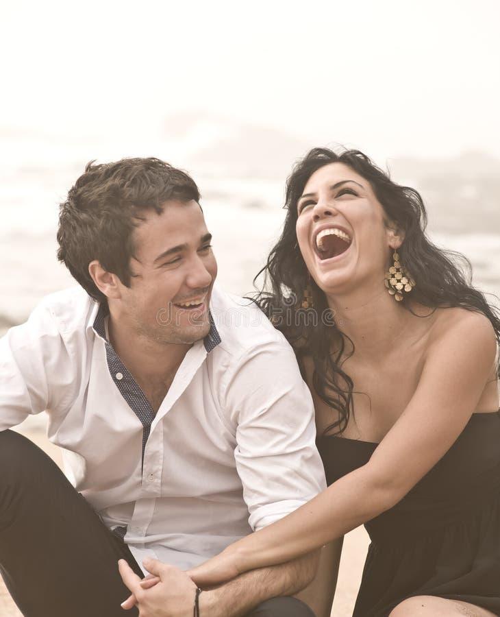 Unga attraktiva par som skrattar på stranden royaltyfri foto