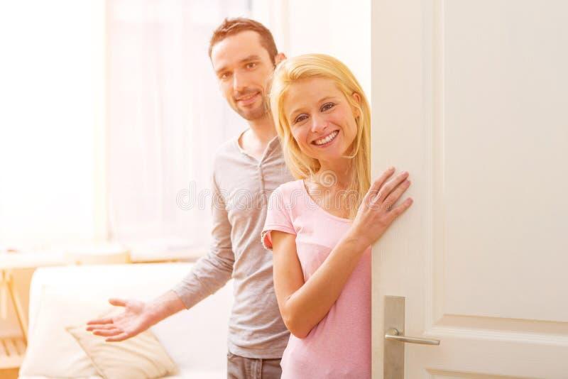 Unga attraktiva par som välkomnar dig i hans hus arkivfoton