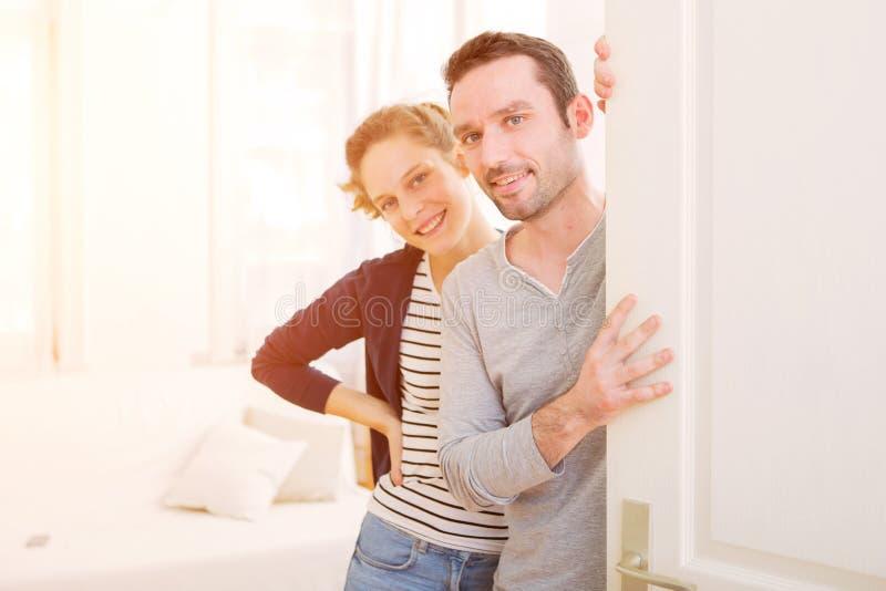 Unga attraktiva par som välkomnar dig i hans hus arkivfoto