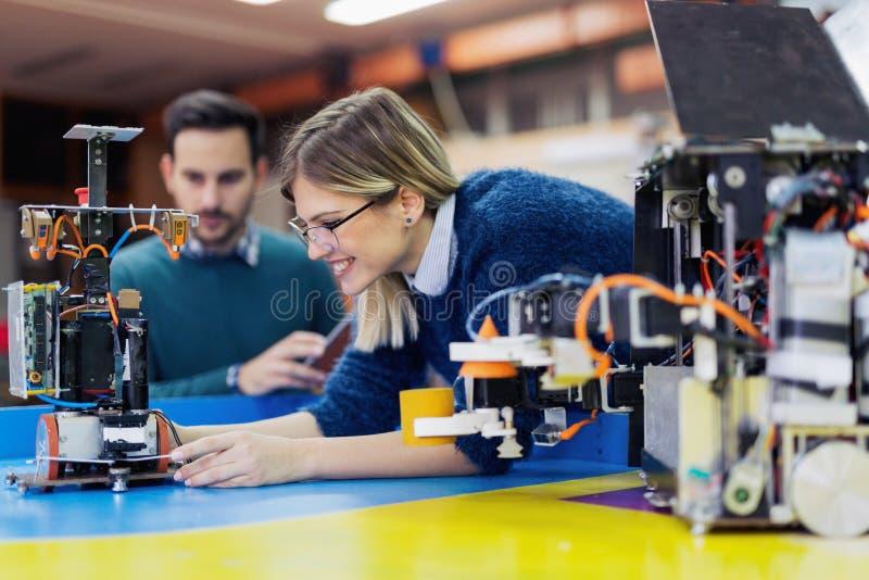 Unga attraktiva studenter av mechatronics som arbetar på projekt arkivbild
