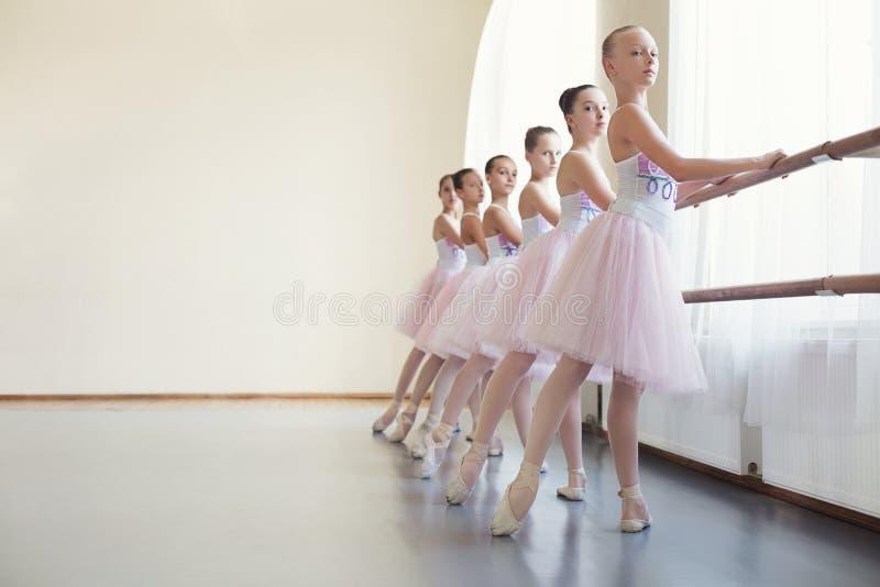 Unga ballerina som repeterar i balettgrupp som utför olika övningar royaltyfri bild