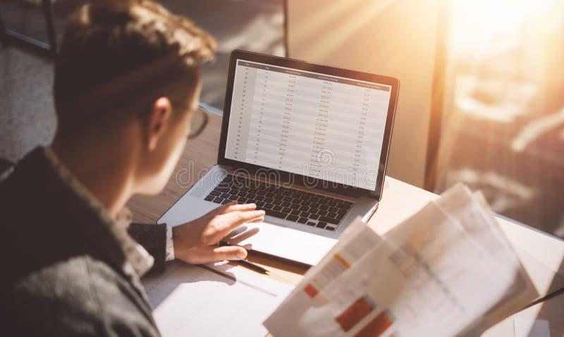 Unga bankrörelsen finansierar analytikeren i glasögon som arbetar på det soliga kontoret på bärbara datorn, medan sitta på trätab fotografering för bildbyråer