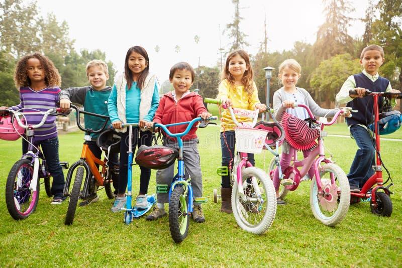 Unga barn med cyklar och sparkcyklar parkerar in royaltyfri foto