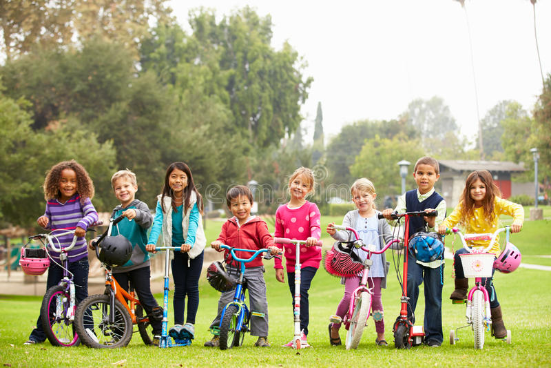 Unga barn med cyklar och sparkcyklar parkerar in arkivbild