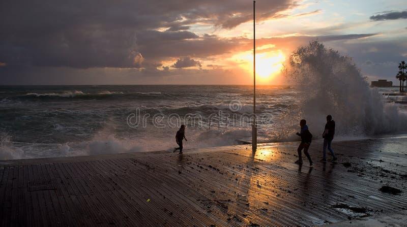 Unga barn som leker på stormiga havet arkivbild