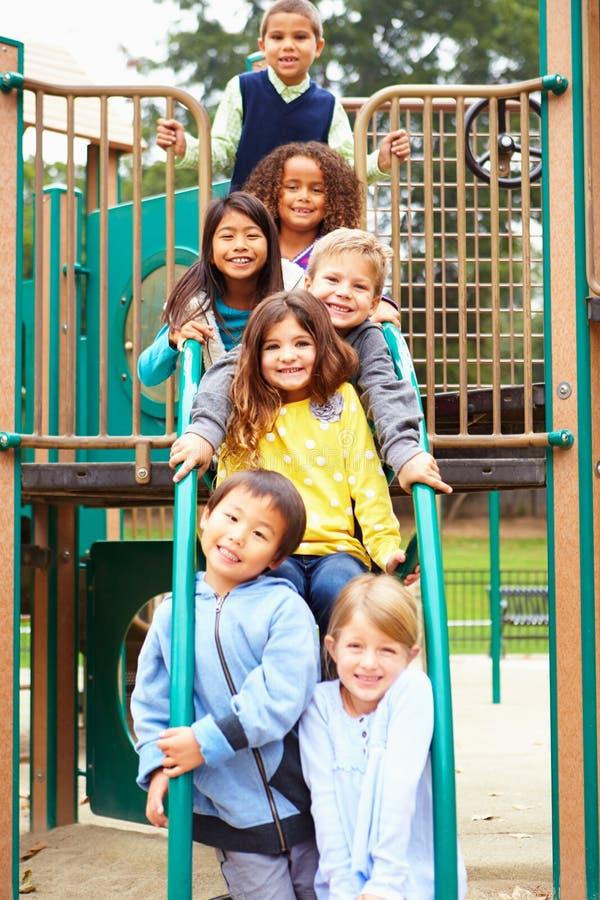 Unga barn som sitter på klättringram i lekplats arkivfoto