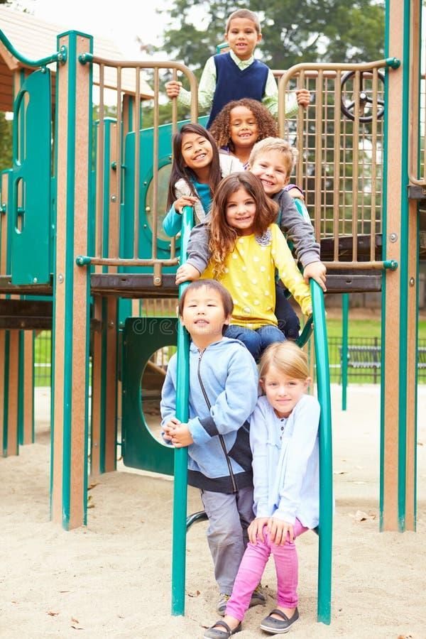 Unga barn som sitter på klättringram i lekplats royaltyfri foto