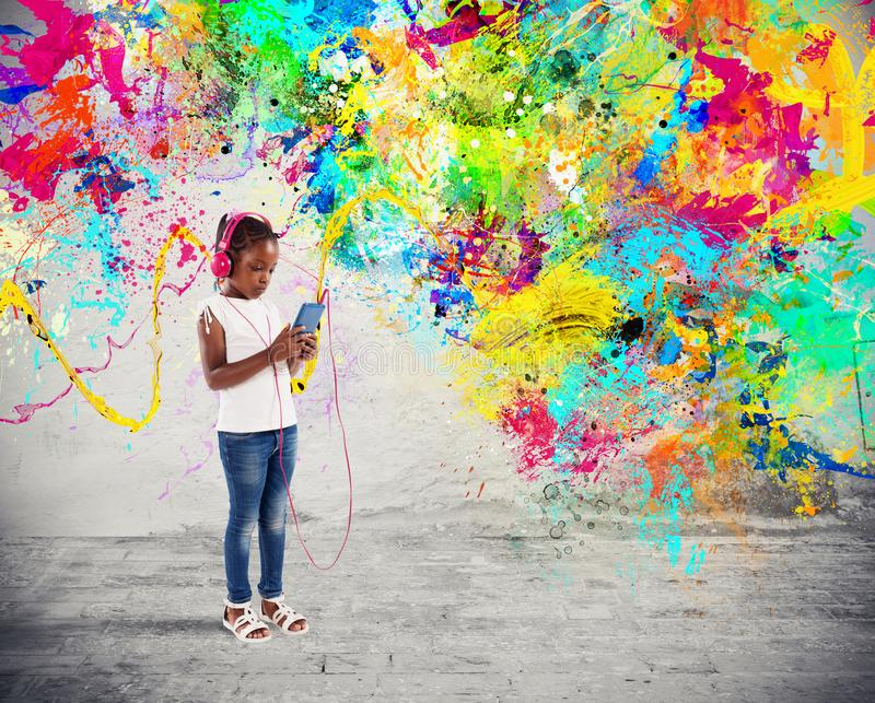 Unga barnet lyssnar till musik med färgstänkeffekter royaltyfria bilder