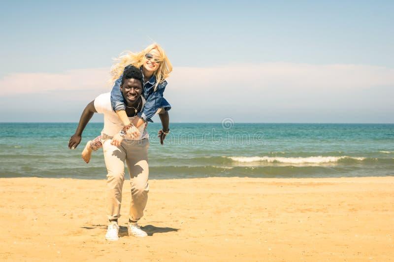 Unga blandras- par på stranden som har gyckel med ridtur på axlarnahopp royaltyfria foton