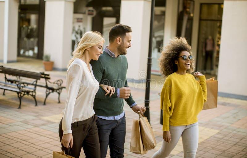 unga blandras- vänner som tillsammans shoppar i galleria arkivfoto