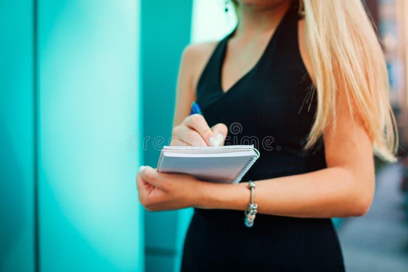 Unga blonda affärskvinnahandstilanmärkningar i notepad Asssistant som sätter ner uppgifter i anteckningsbok royaltyfri foto