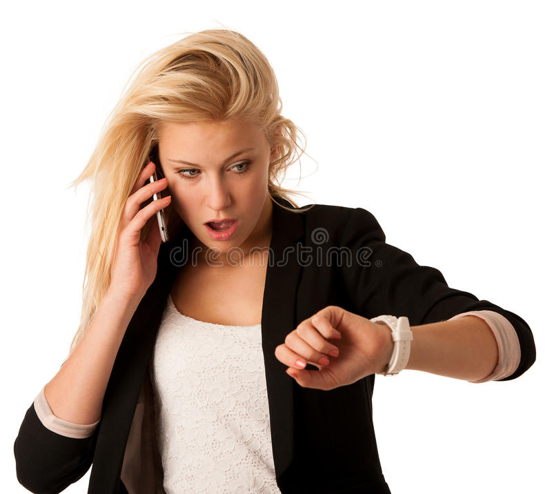 Unga blonda kvinnablickar på hennes klocka, när hon skulle vara sen iso arkivfoton