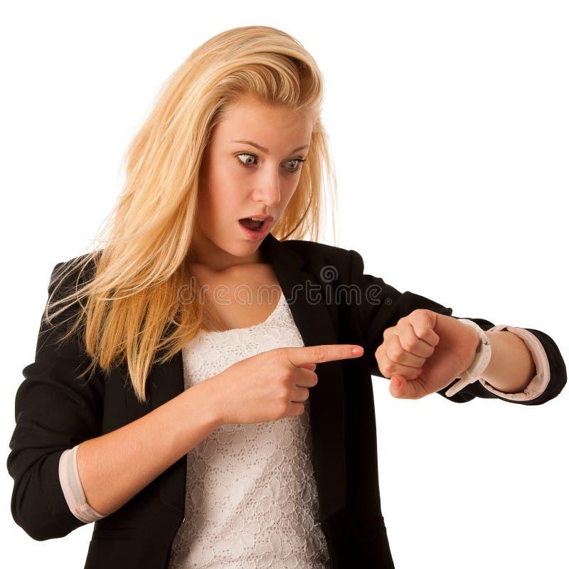 Unga blonda kvinnablickar på hennes klocka, när hon skulle vara sen iso royaltyfri foto