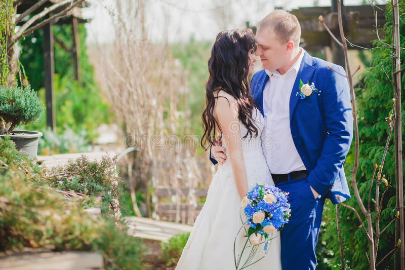 Unga brölloppar som tycker om romantiska ögonblick utanför på en sommaräng arkivbild