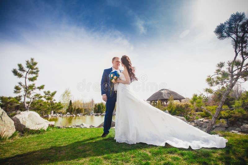 Unga brölloppar som tycker om romantiska ögonblick utanför på en sommaräng arkivbilder
