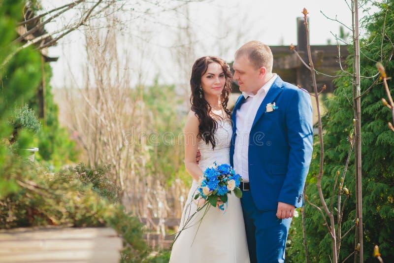 Unga brölloppar som tycker om romantiska ögonblick utanför på en sommaräng arkivfoto