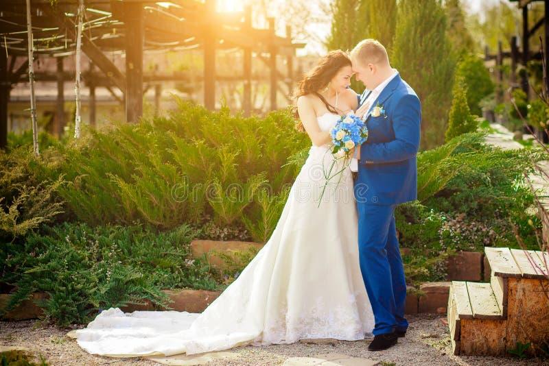Unga brölloppar som tycker om romantiska ögonblick utanför på en sommaräng royaltyfri foto