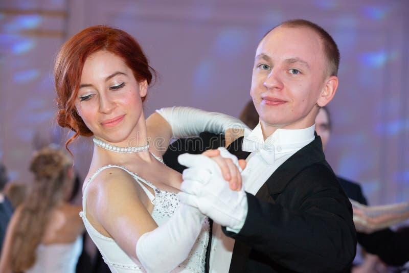 Unga bra seende par i aftonklänningen och klänninglaget som poserar i elegant väg i en klassisk stil arkivbild