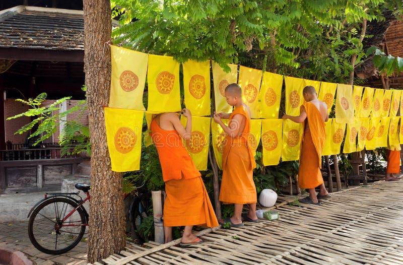 Unga buddistiska munkar som gör dagligt arbete i trädgård av templet med festliga flaggor arkivfoton