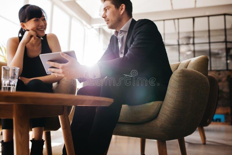 Unga businesspeople som använder den digitala minnestavlan i lobby royaltyfri fotografi