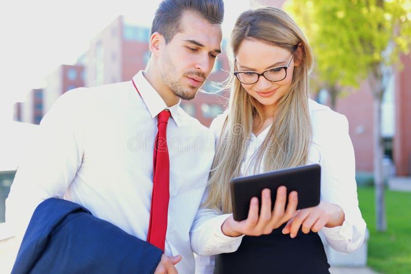 Unga businesspeople som använder den utomhus- digitala minnestavlan arkivbild
