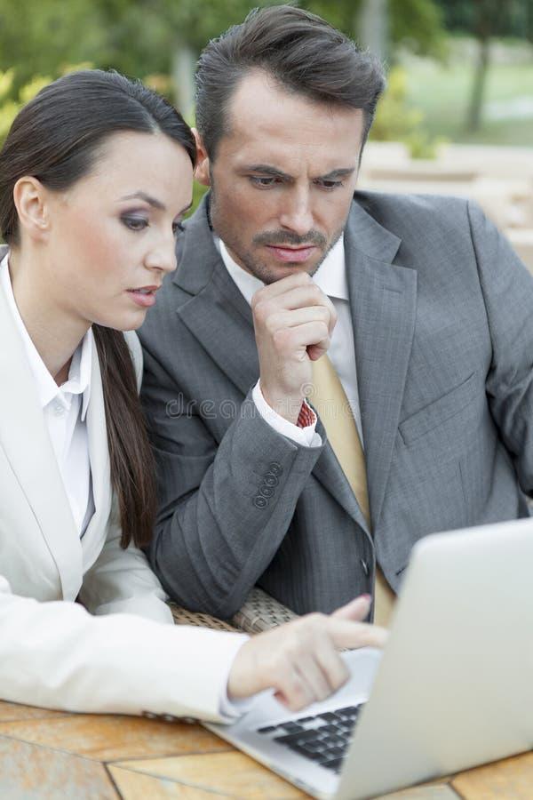 Unga businesspeople som utomhus diskuterar över bärbara datorn arkivfoton