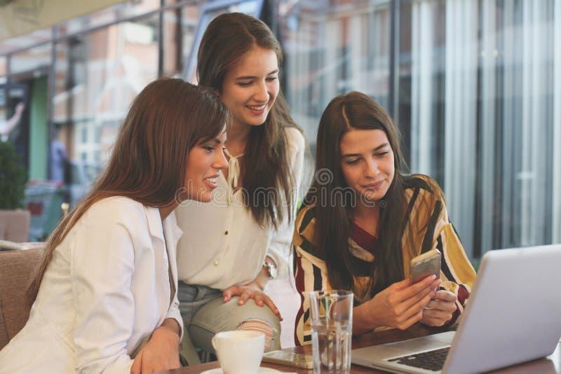 unga cafekvinnor smart använda för telefon arkivbild