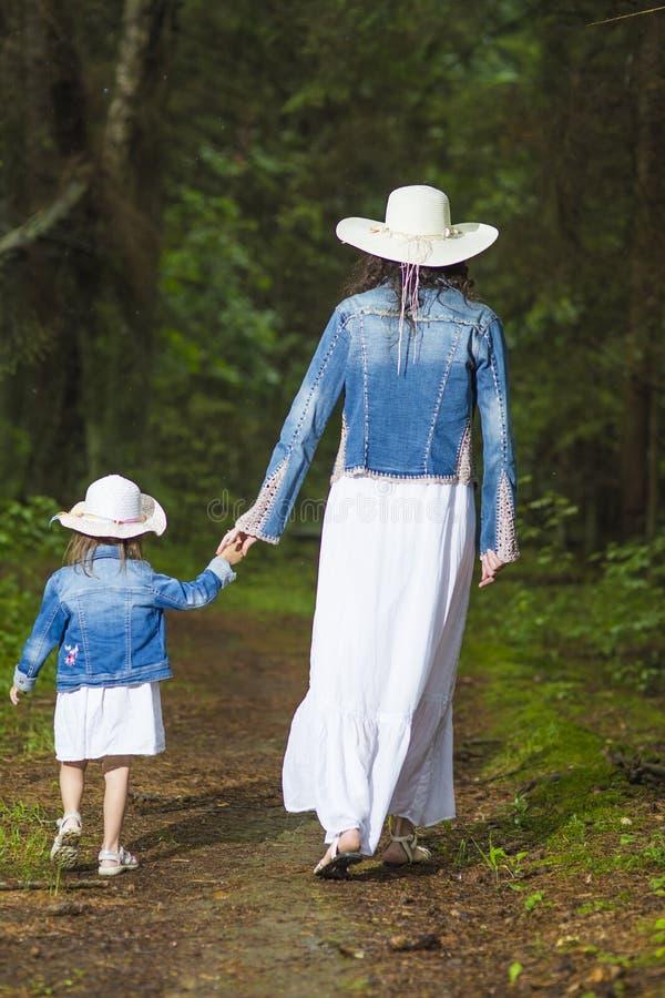 Unga caucasian par av modern och dottern som tar en promenad i grön sommarskog arkivbilder