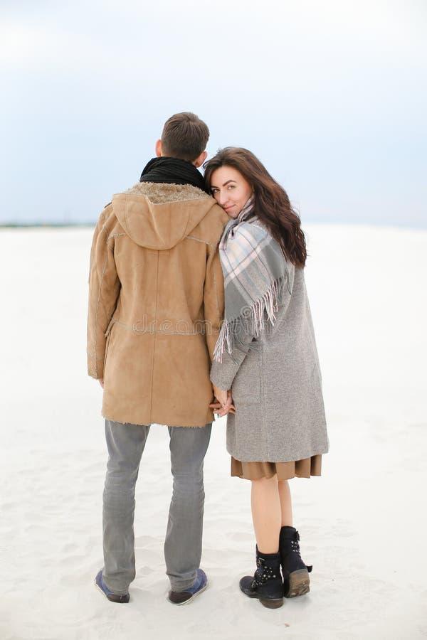 Unga caucasian par som går på vinter, snöar bakgrund, bärande lag och halsdukar arkivbild