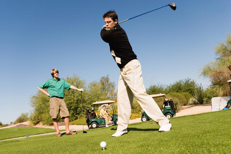 Unga Caucasian vänner som leker Golf royaltyfri fotografi