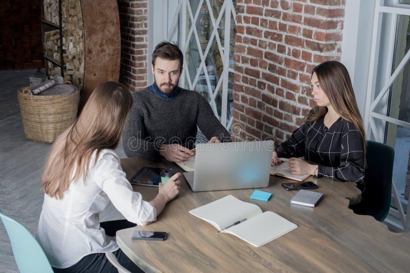 Unga coworkers som har utbildningskurs genom att använda den moderna bärbar datordatoren för sparande information royaltyfri bild