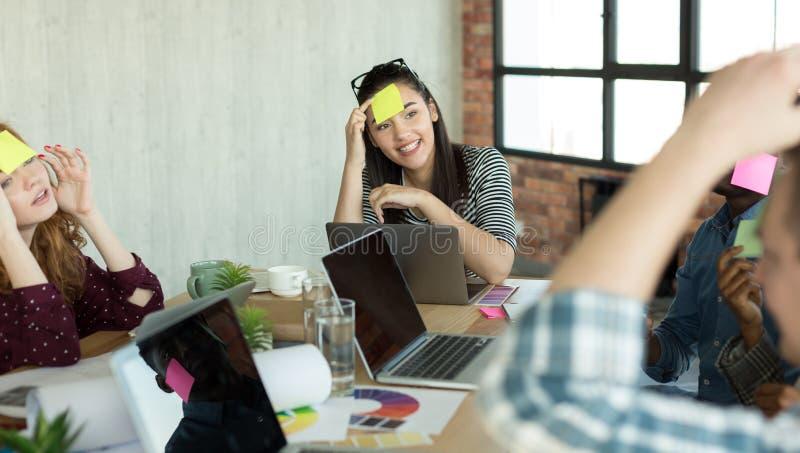 Unga coworkers som spelar leken med pappers- klistermärkear på pannan royaltyfri foto