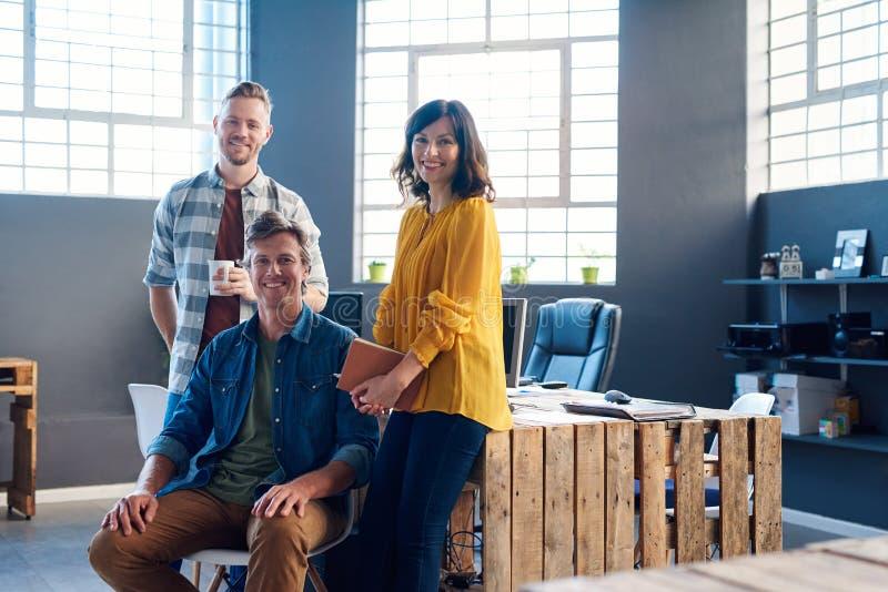 Unga coworkers som tillsammans ler i ett modernt kontor royaltyfria bilder