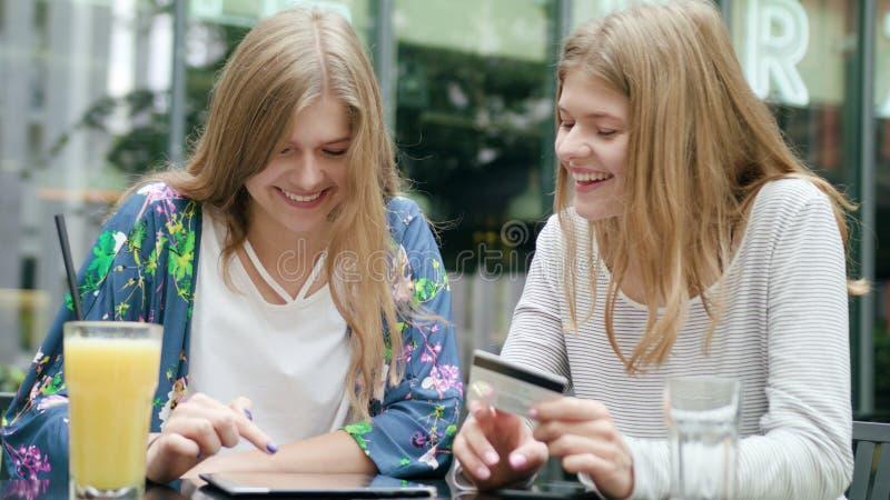 Unga damer som använder en minnestavla och rymmer kreditkorten royaltyfri foto