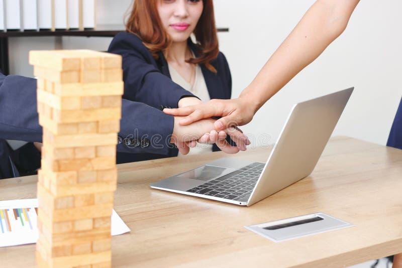 Unga det sammanfogade affärsfolket räcker tillsammans till att hälsa färdigt handla i regeringsställning Framgång- och teamworkbe arkivfoton