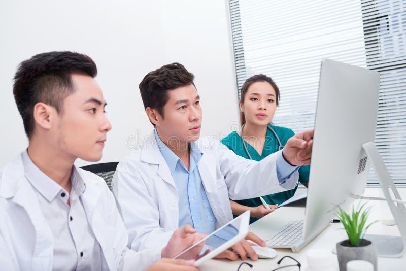 Unga doktorer som använder datoren i sjukhuskontor royaltyfri fotografi